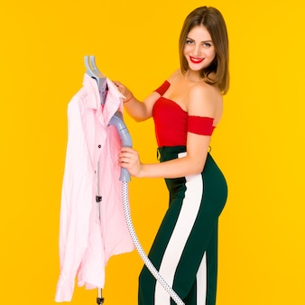 Young woman steaming pink shirt at dry-cleaner's on yellow background