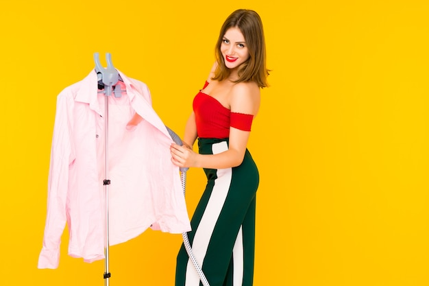 Young woman steaming pink shirt at dry-cleaner's on yellow