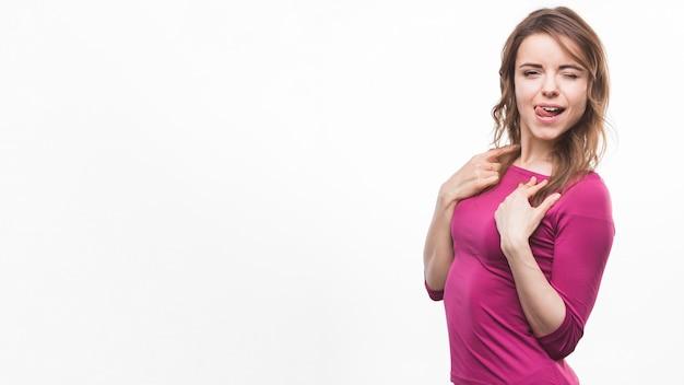 Giovane donna che attacca la sua lingua fuori posa su sfondo bianco