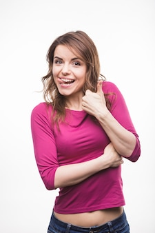 Young woman sticking her tongue out showing thumb up sign