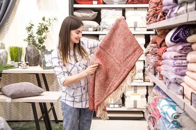 Una giovane donna in un negozio sceglie i tessuti. il concetto di acquisto di una casa.