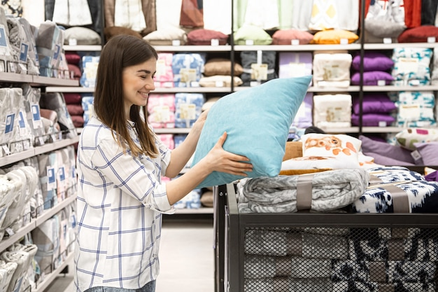 A young woman in a store chooses textiles.