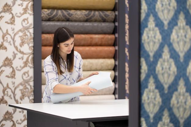 Una giovane donna in un negozio sceglie wallpaper per la sua casa. c