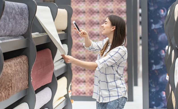 A young woman in a store chooses wallpaper for her home. concept of repair and shopping.