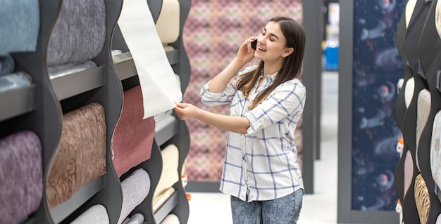 A young woman in a store chooses wallpaper for her home