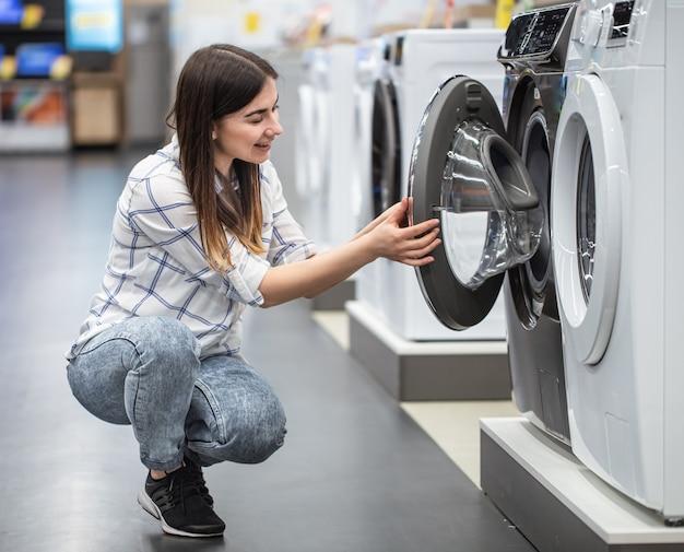 Una giovane donna in un negozio sceglie una lavatrice .. il concetto di shopping.