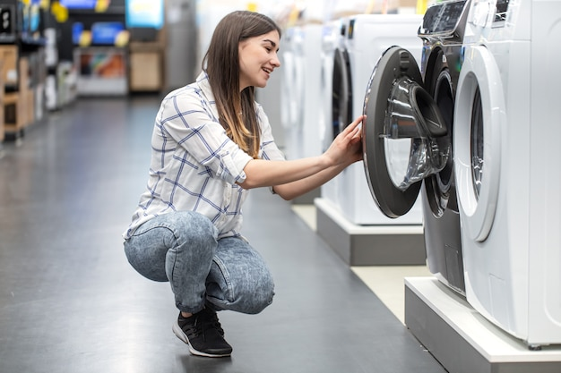 A young woman in a store chooses a washing machine.