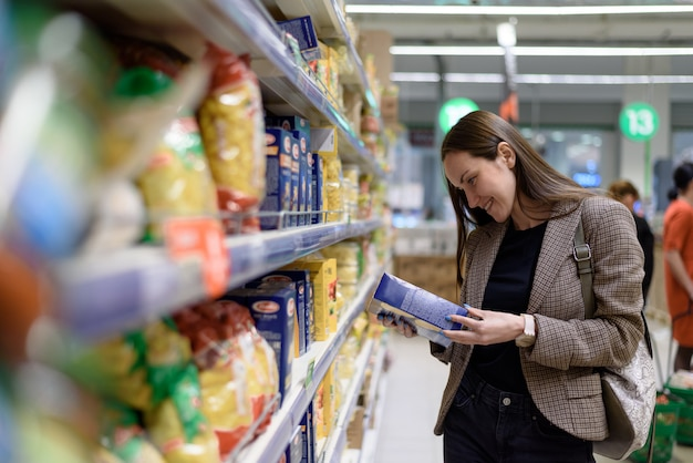 A young woman in the store reads the label of pasta in the package