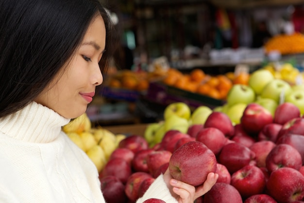 Young woman at store with apples in hand