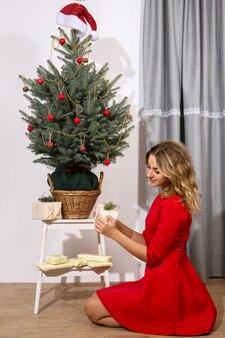 젊은 여자는 크리스마스 트리 아래 선물을 stows