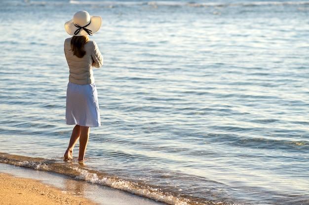 Young woman in straw hat and a dress standing alone on empty sand beach at sea shore. lonely tourist girl looking at horizon over calm ocean surface on vacation trip.