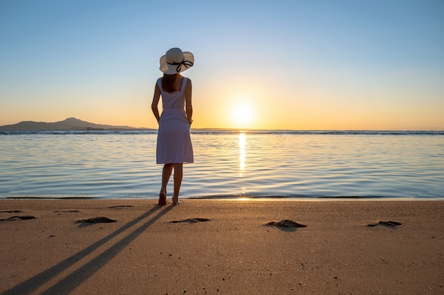 Young woman in straw hat and a dress standing alone on empty sand beach at sunset sea shore. lonely girl looking at horizon over calm ocean surface on vacation trip.