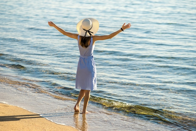 Young woman in straw hat and a dress standing raising hands on empty sand beach at sea shore