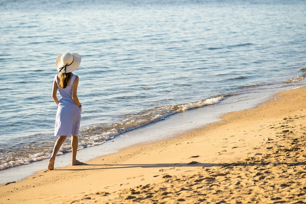 Young woman in straw hat and a dress walking alone on empty sand beach at sea shore. lonely tourist girl looking at horizon over calm ocean surface on vacation trip.