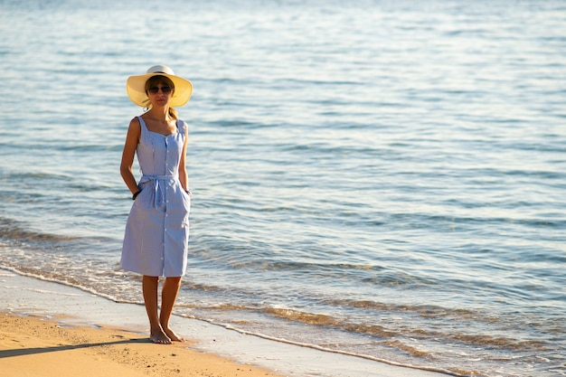 Young woman in straw hat and a dress walking alone on empty sand beach at sea shore. lonely tourist woman looking at horizon over calm ocean surface on vacation trip.