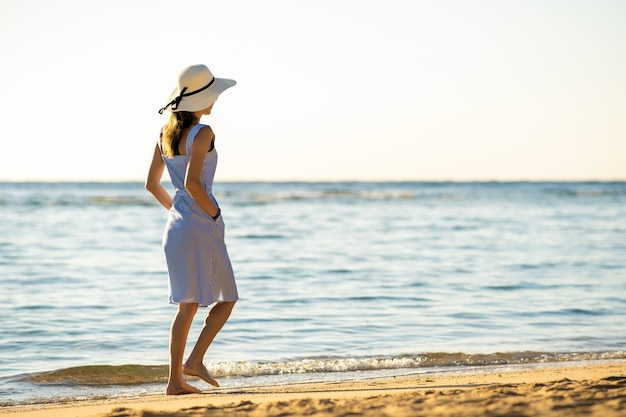 Young woman in straw hat and a dress walking alone on empty sand beach at sea shore.