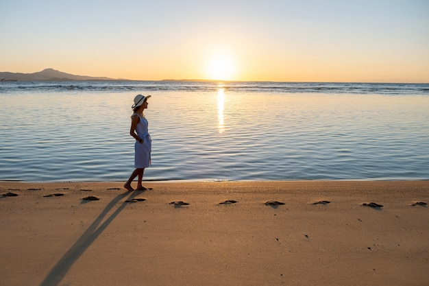 Young woman in straw hat and a dress walking alone on empty sand beach at sunset sea shore. lonely girl looking at horizon over calm ocean surface on vacation trip.