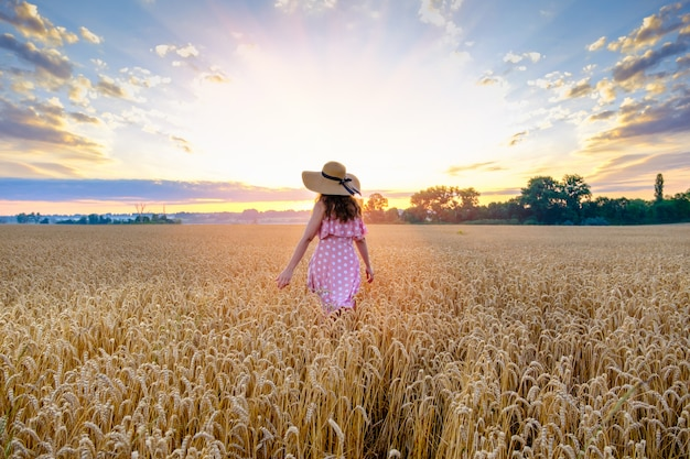 Young woman in a straw hat on her head walks across a wheat field with her back to the camera on sunrise. copy space