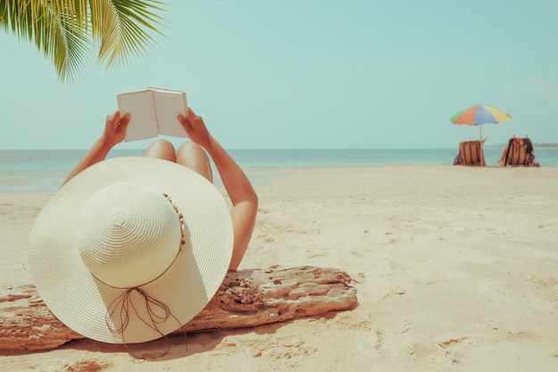 Young woman in straw hat lying sunbathe on a tropical beach