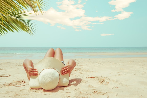 Young woman in straw hat lying sunbathe on a tropical beach.