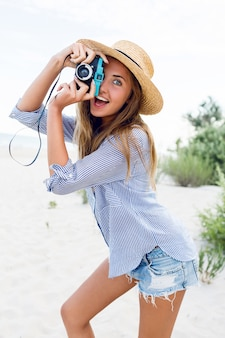Young woman in straw hat making picture with retro camera on the beach