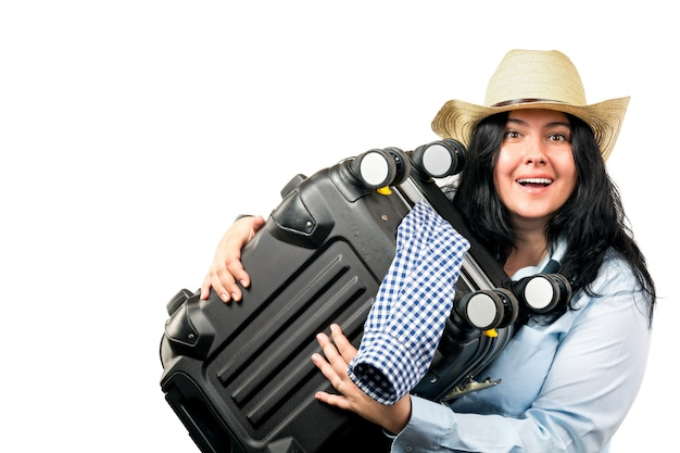 Young woman in straw hat smiling and holding suitcase