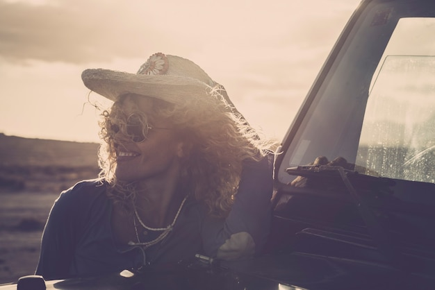 Young woman in straw hat smiling while leaning on car during sunset. cheerful woman relaxing during road trip. happy hipster woman in hat with curly hair admiring view while leaning on car