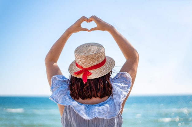Young woman in a straw hat and a summer dress backs view makes love sign with her hands on blue sea