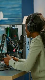オープンチャットのストリーミングでチームメートと話しているジョイスティックでビデオゲームをプレイする若い女性ストリーマー