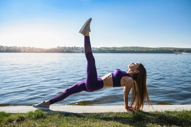 Молодая женщина растягивает ноги рано утром перед работой на открытом воздухе