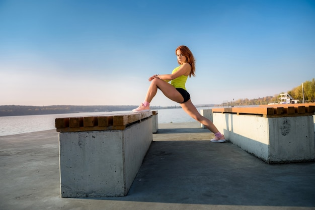 야외에서 작업 시간 전에 이른 아침 젊은 여자 streching 다리.
