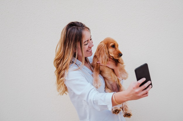 Young woman at the street with her cocker dog taking a picture with mobile phone. lifestyle outdoors with pets