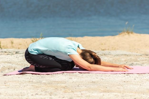 Молодая женщина растягивается и разминается на розовом коврике у моря