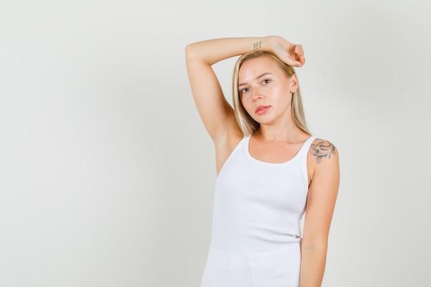 白い一重項で頭の周りに腕を伸ばす若い女性