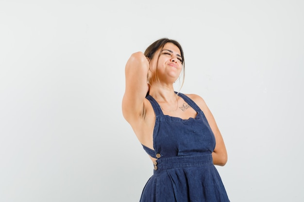 Young woman stretching arms in dress and looking relaxed