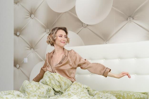 Молодая женщина протягивает руки, сидя на кровати в домашней спальне, глядя в сторону
