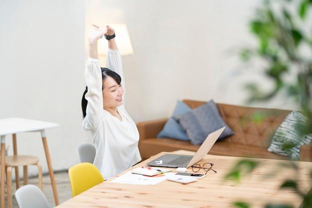 カジュアルな空間で仕事でストレッチ若い女性
