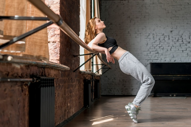 Young woman stretching on barre in the studio