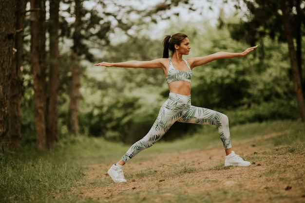 Young woman stretching and breathing fresh air in middle of forest while exercising