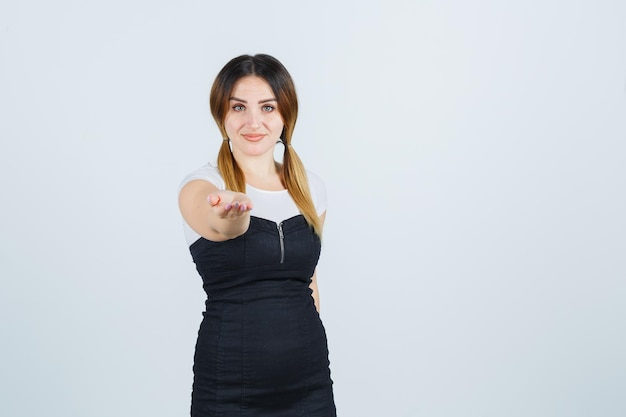 Giovane donna che allunga la mano a coppa mentre sta ricevendo qualcosa