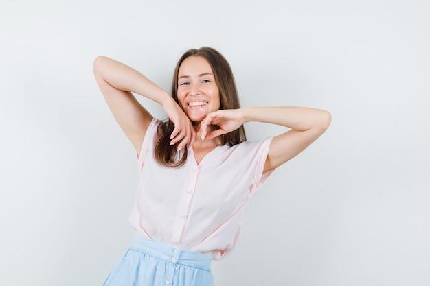 T- 셔츠, 치마에 팔꿈치를 스트레칭 하 고 즐거운 찾고 젊은 여자. 전면보기.