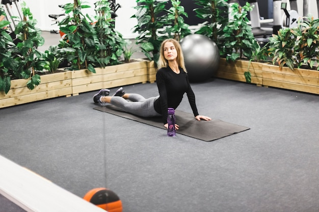 Young woman stretching on exercising mat