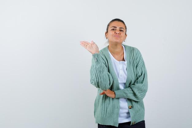 白いシャツとミントグリーンのカーディガンで挨拶として手を伸ばして幸せそうに見える若い女性