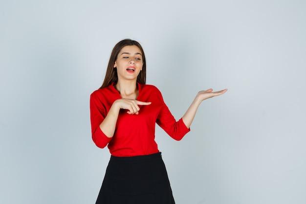 상상의 뭔가를 들고 손을 스트레칭, 오른쪽을 가리키는 젊은 여자