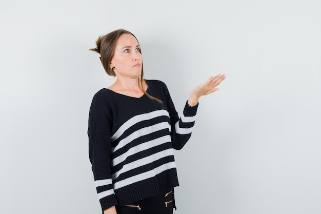 Young woman stretching hand as trying to understand something in striped knitwear and black pants and looking surprised