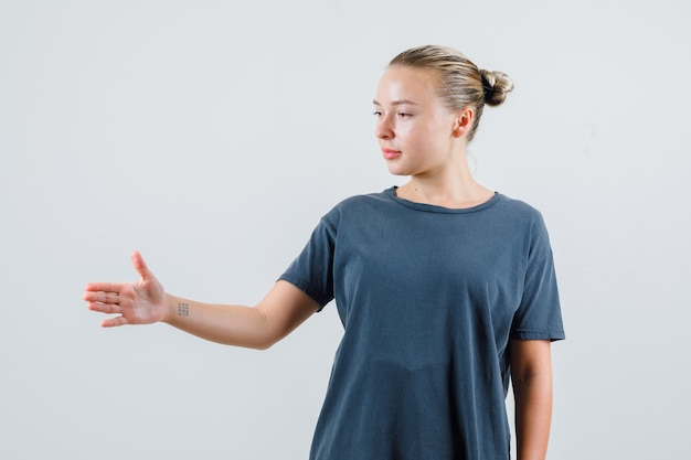 灰色のtシャツを振って、フレンドリーに見えるために手を伸ばす若い女性