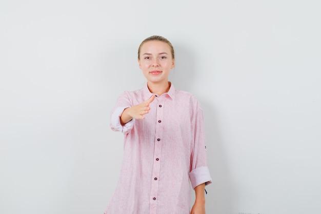 Молодая женщина протягивает руку для тряски в розовой рубашке и выглядит вежливо