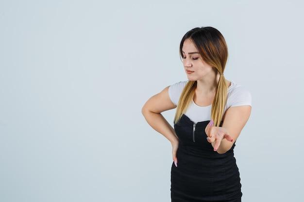 Giovane donna che allunga la mano in un gesto perplesso