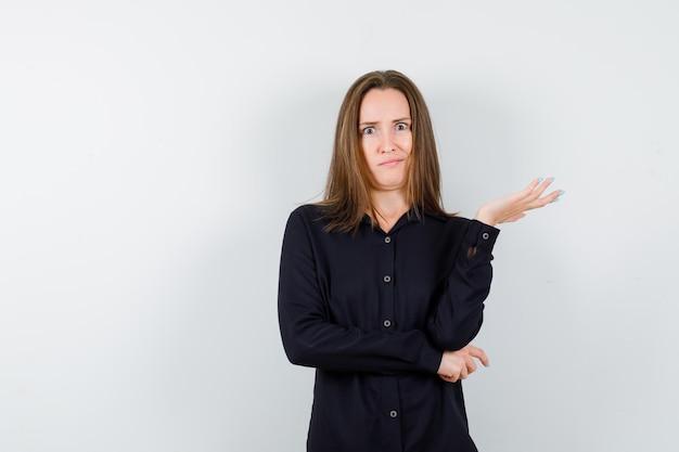 Giovane donna che allunga la mano in modo interrogativo