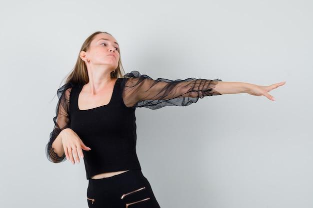 Giovane donna che allunga la mano sul lato destro in camicetta nera e pantaloni neri e sembra dispiaciuta